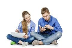 Muchacho y muchacha adolescentes de la edad con la tableta y el cuaderno Fotografía de archivo