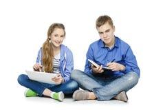 Muchacho y muchacha adolescentes de la edad con la tableta y el cuaderno Fotos de archivo libres de regalías