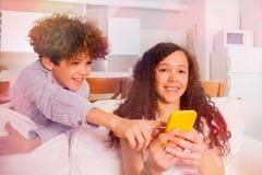 Muchacho y muchacha alegres con el teléfono celular en el sofá Fotografía de archivo libre de regalías