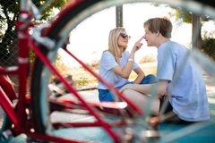 Muchacho y muchacha alegres en las gafas de sol que se sientan en piso y que juegan feliz junto Pares hermosos jovenes que se div Fotografía de archivo