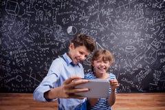Muchacho y muchacha con el smartphone, tomando el selfie, contra la pizarra Foto de archivo libre de regalías