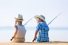 Muchacho y muchacha con las cañas de pescar Fotografía de archivo libre de regalías