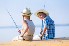 Muchacho y muchacha con las cañas de pescar Fotos de archivo libres de regalías