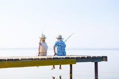 Muchacho y muchacha con las cañas de pescar Imágenes de archivo libres de regalías