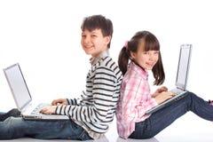 Muchacho y muchacha con las computadoras portátiles imágenes de archivo libres de regalías