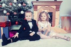 Muchacho y muchacha con los regalos cerca del árbol de navidad Imagen de archivo libre de regalías