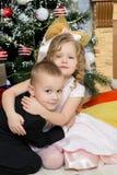 Muchacho y muchacha con los regalos cerca del árbol de navidad Fotografía de archivo