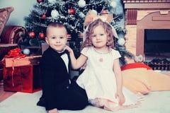 Muchacho y muchacha con los regalos cerca del árbol de navidad Foto de archivo libre de regalías