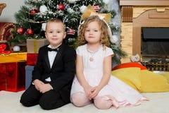 Muchacho y muchacha con los regalos cerca del árbol de navidad Imágenes de archivo libres de regalías