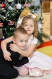 Muchacho y muchacha con los regalos cerca del árbol de navidad Imagen de archivo