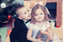 Muchacho y muchacha con los regalos cerca del árbol de navidad Fotos de archivo