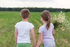 Muchacho y muchacha con un ramo de margaritas imagen de archivo libre de regalías
