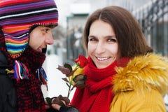Muchacho y muchacha con una rosa en invierno Fotos de archivo libres de regalías