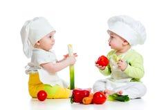 Muchacho y muchacha de bebés con las verduras Fotos de archivo libres de regalías