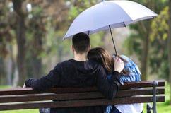 Muchacho y muchacha de día lluvioso que se sientan en banco y que llevan a cabo el umbrell azul Fotografía de archivo libre de regalías