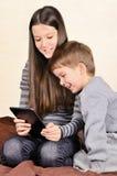 Muchacho y muchacha de risa que juegan en la tableta Imagen de archivo