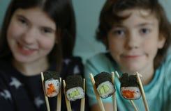 Muchacho y muchacha del adolescente con el rollo de sushi japonés Imagen de archivo