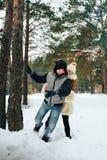 Muchacho y muchacha del adolescente que se divierten en bosque del invierno Imagen de archivo libre de regalías