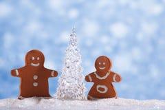 Muchacho y muchacha del pan de jengibre con el árbol de navidad del vidrio del hockey shinny Fotografía de archivo