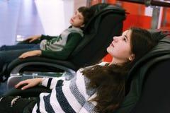 Muchacho y muchacha en cierre de la silla del masaje encima de la foto Fotografía de archivo