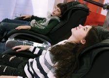 Muchacho y muchacha en cierre de la silla del masaje encima de la foto Fotos de archivo