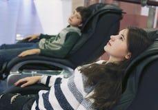 Muchacho y muchacha en cierre de la silla del masaje encima de la foto Imágenes de archivo libres de regalías