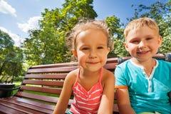 Muchacho y muchacha en el banco en parque Foto de archivo libre de regalías