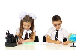 Muchacho y muchacha en el escritorio Fotografía de archivo
