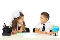 Muchacho y muchacha en el escritorio Imágenes de archivo libres de regalías