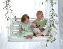 Muchacho y muchacha en el oscilación con el conejito Fotos de archivo libres de regalías