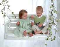 Muchacho y muchacha en el oscilación con el conejito Fotografía de archivo libre de regalías