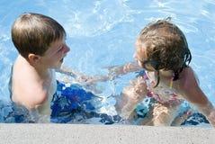 Muchacho y muchacha en hablar de la piscina Imagen de archivo