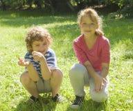 Muchacho y muchacha en hierba Fotos de archivo