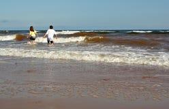 Muchacho y muchacha en la playa Foto de archivo