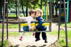 Muchacho y muchacha en los oscilaciones Imagenes de archivo