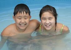 Muchacho y muchacha en una piscina Imagen de archivo libre de regalías