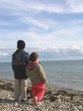 Muchacho y muchacha en una playa en invierno fotografía de archivo