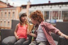 Muchacho y muchacha felices con helado Imagen de archivo