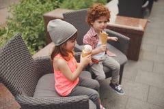 Muchacho y muchacha felices con helado Fotos de archivo