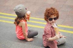 Muchacho y muchacha felices con helado Imagenes de archivo