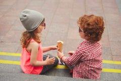 Muchacho y muchacha felices con helado Foto de archivo