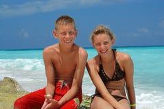 Muchacho y muchacha felices en la playa Foto de archivo