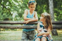 Muchacho y muchacha feliz que se sientan en el banco imágenes de archivo libres de regalías