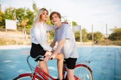 Muchacho y muchacha hermosos con el pelo rubio en la bicicleta que mira feliz in camera que pasa el tiempo junto en la cancha de  Fotos de archivo libres de regalías