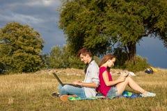 Muchacho y muchacha jovenes en parque con el ordenador portátil y el libro Imagenes de archivo