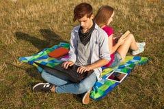 Muchacho y muchacha jovenes en parque con el ordenador portátil y el libro Fotografía de archivo