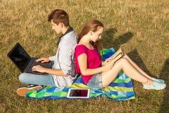 Muchacho y muchacha jovenes en parque con el ordenador portátil y el libro Imágenes de archivo libres de regalías