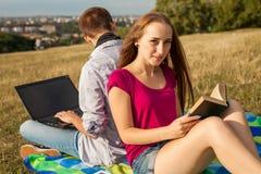 Muchacho y muchacha jovenes en parque con el ordenador portátil y el libro Imagen de archivo
