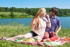 Muchacho y muchacha jovenes en una comida campestre por el lago Foto de archivo libre de regalías