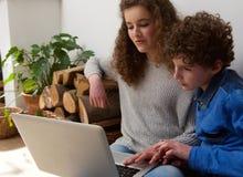 Muchacho y muchacha jovenes que usa el ordenador portátil junto Fotos de archivo libres de regalías